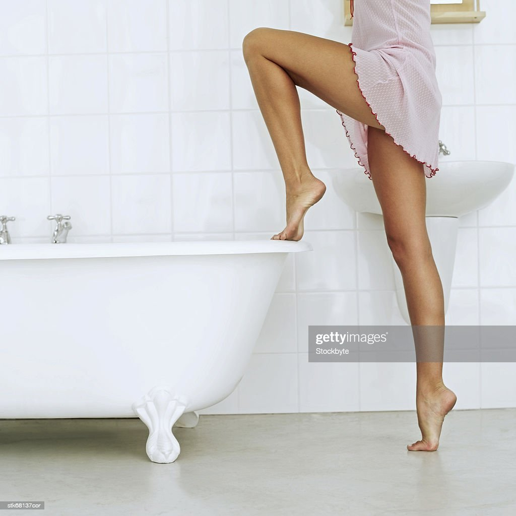 side profile of a woman placing her foot on a bath tube : Stock Photo