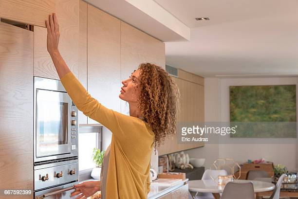 Side profile of a woman working in the kitchen