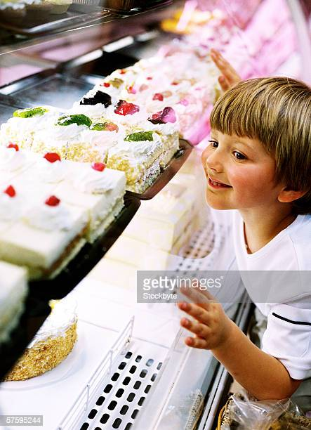Side profile of a young boy (4-6) leaning on the display window of a bakery
