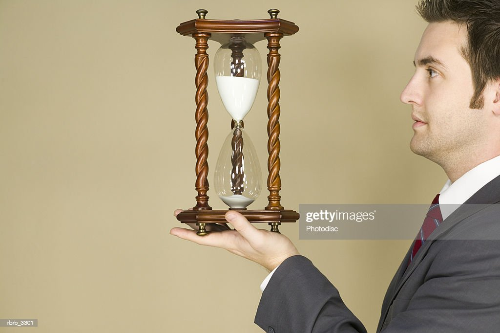 Side profile of a young businessman holding an hourglass : Foto de stock