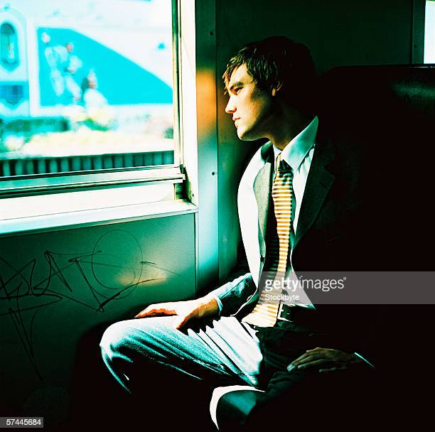 side profile of a young businessman looking out the window of a commuter train - vandalismus stock-fotos und bilder