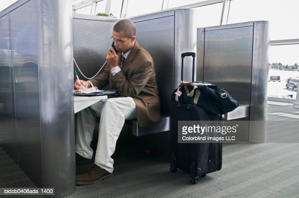 Side profile of a young businessman using a phone booth in an airport
