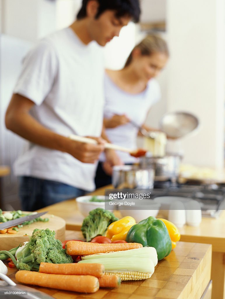 side profile of a young couple cooking food in the kitchen : Stock Photo