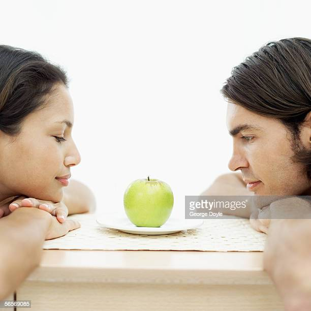 side profile of a young couple looking at a green apple on a table