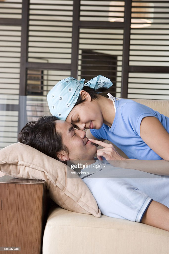 side profile of a young couple romancing on a couch stock photo