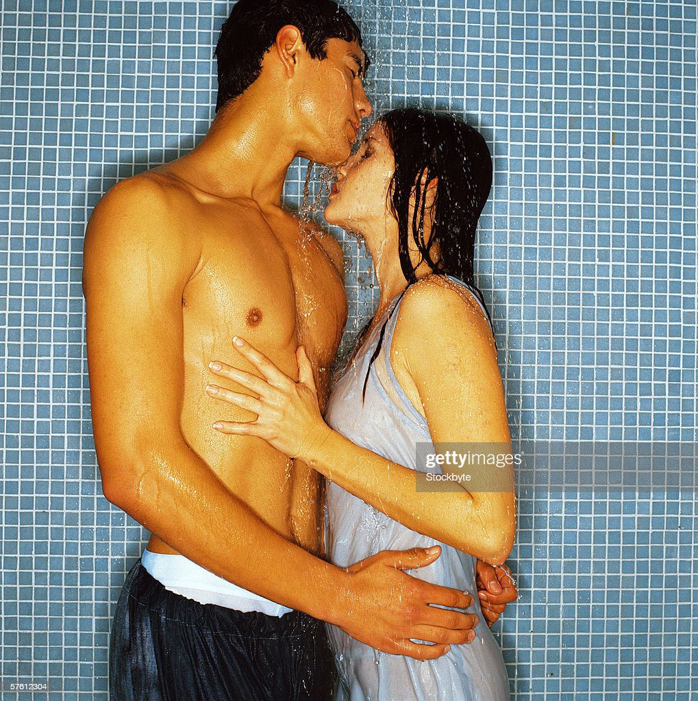 Side profile of a young couple showering together : Stock Photo
