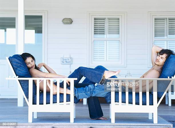 side profile of a young couple sleeping on deck chairs