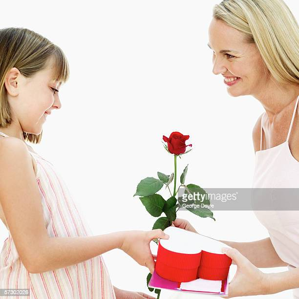 Side profile of a young girl (8-10) giving her mother valentine gifts