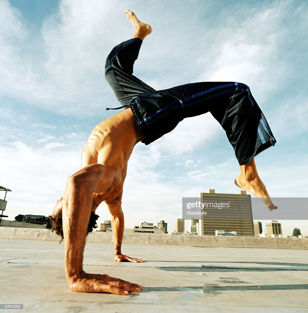 Side profile of a young man doing headstand : Stock Photo