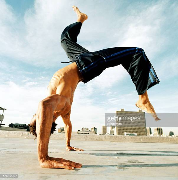 Side profile of a young man doing headstand