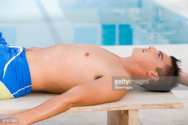Side profile of a young man lying on a bench at the poolside