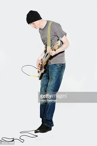 Side profile of a young man playing a guitar, Moscow, Russia