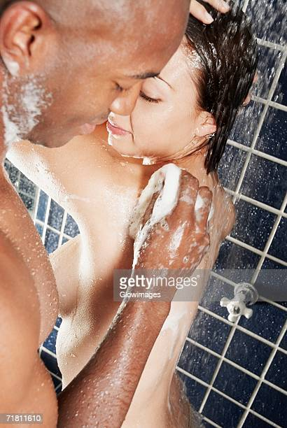 Side profile of a young man scrubbing a young woman's back with a sponge