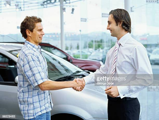 side profile of a young man shaking hands with a car dealer