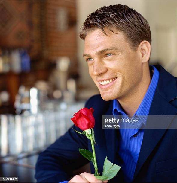 side profile of a young man sitting in a restaurant holding a rose