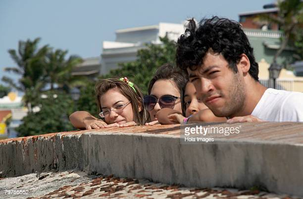 side profile of a young man with three young women looking over a castle wall, morro castle, old san juan, san juan, puerto rico - old san juan wall stock photos and pictures