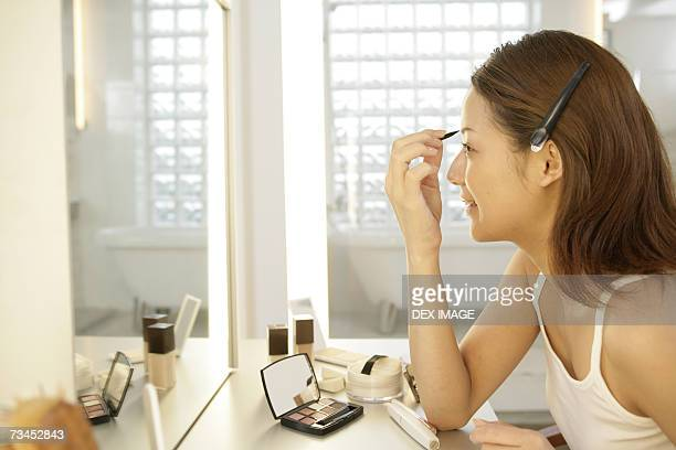 Side profile of a young woman applying make-up in front of a dressing table