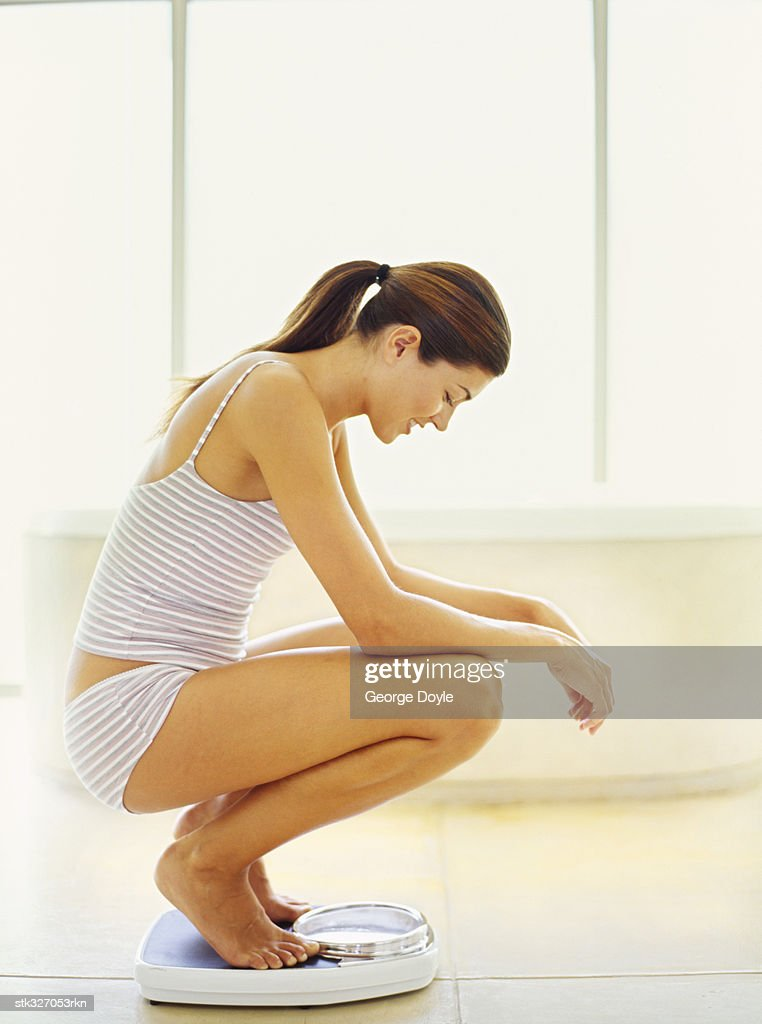 side profile of a young woman crouching on a weight scale : Stock Photo