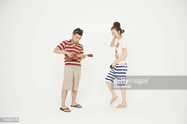 side profile of a young woman dancing and a young man playing a toy guitar - percussion instrument stock pictures, royalty-free photos & images