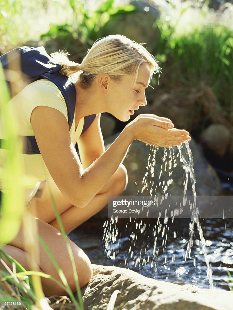 Side profile of a young woman drinking water from a stream : Stock Photo