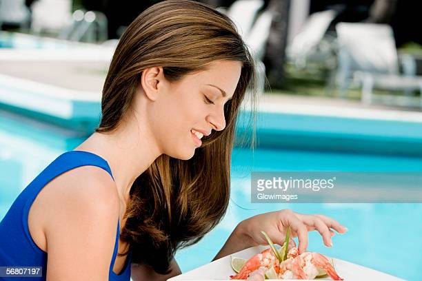 Side profile of a young woman eating shrimps