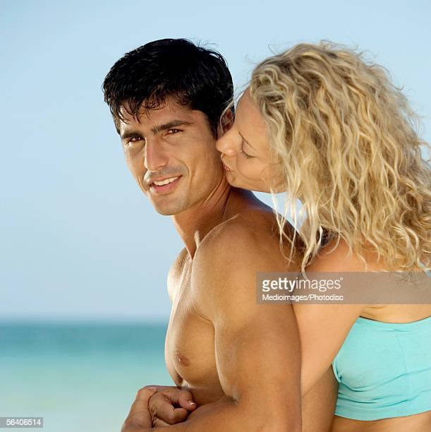 Side profile of a young woman embracing a young man from behind on the beach