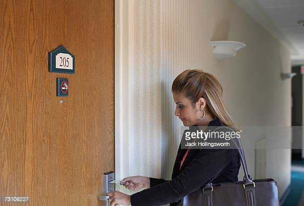 Side profile of a young woman entering a keycard into a hotel room door