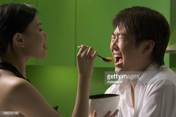 Side profile of a young woman feeding a young man fruit with a spoon