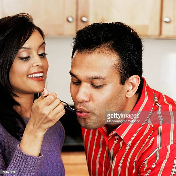 Side profile of a young woman feeding a young man with a spoon