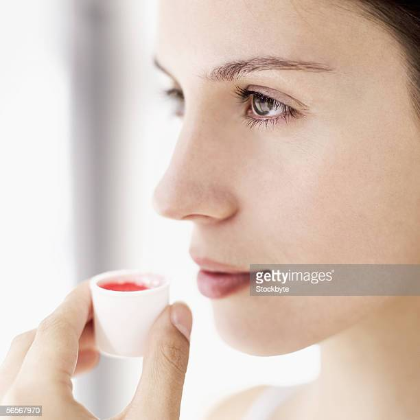 side profile of a young woman holding a cup of mouthwash
