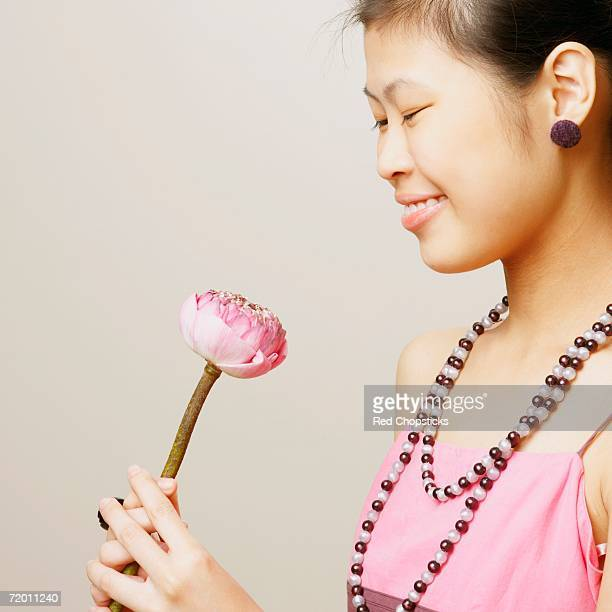 Side profile of a young woman holding a lotus flower