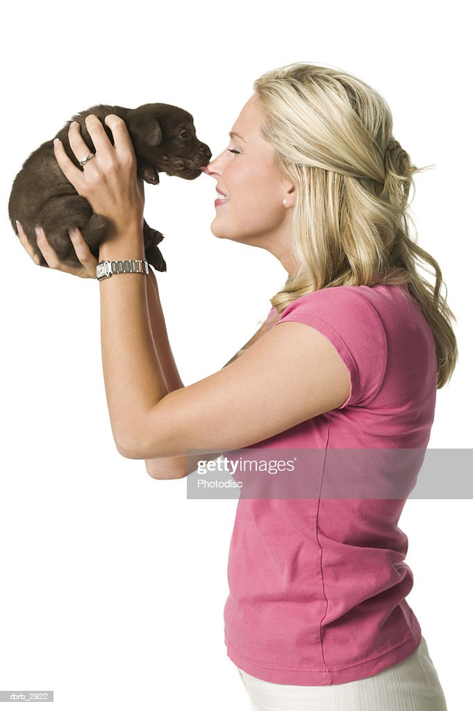 Side profile of a young woman holding a puppy : Foto de stock