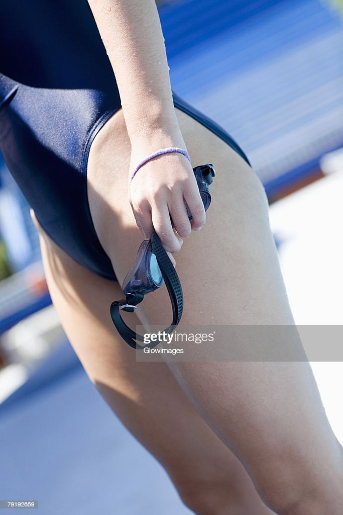Side profile of a young woman holding swimming goggles at the poolside : Stock Photo