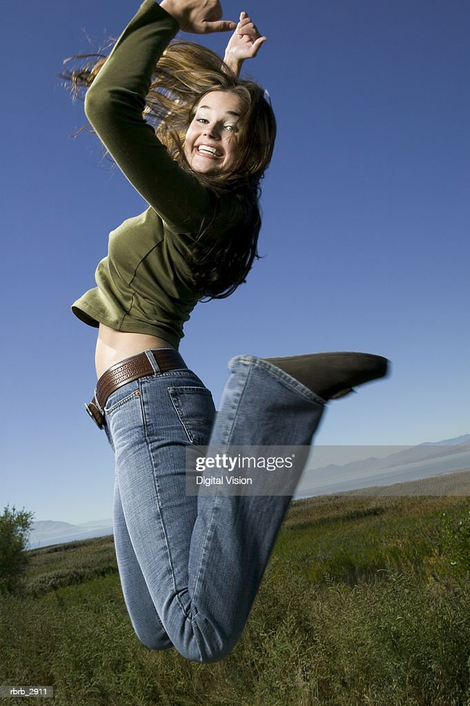 Side profile of a young woman jumping on a grassy field with her arms raised : Foto de stock