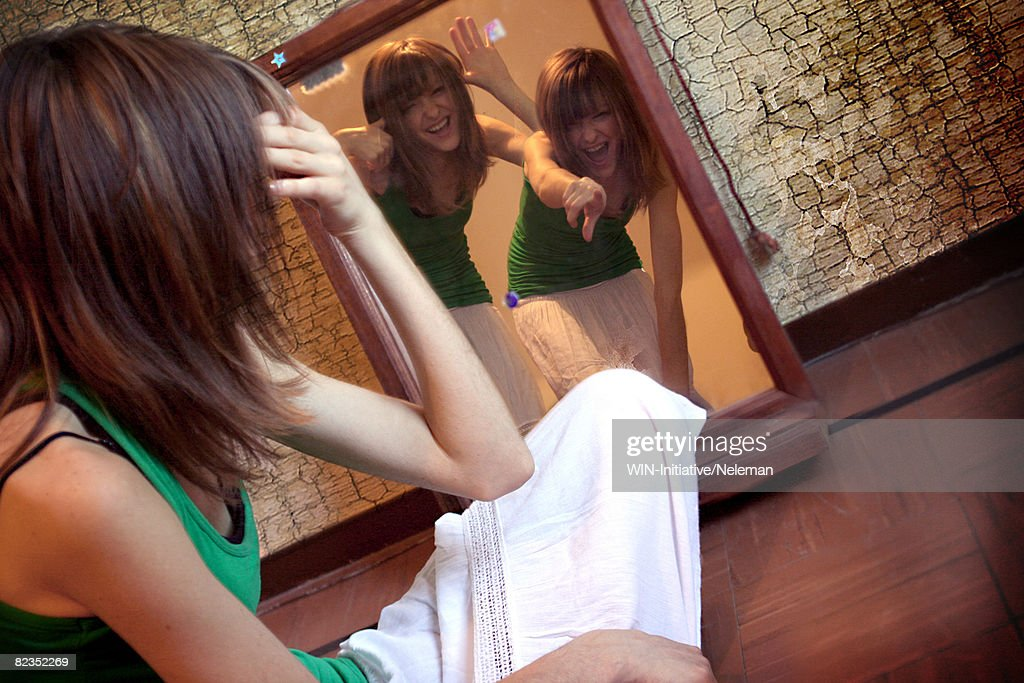 Side profile of a young woman looking at her reflections in a mirror, Buenos Aires, Argentina : Stock Photo