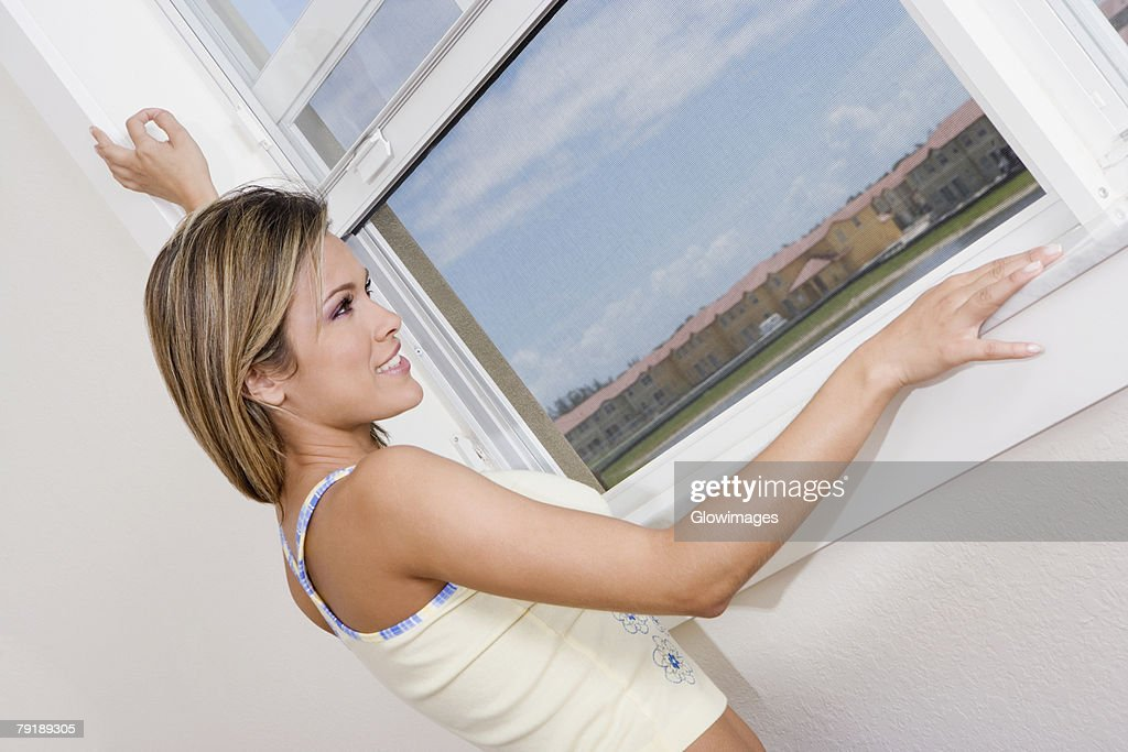 Side profile of a young woman looking through a window and smiling : Stock Photo