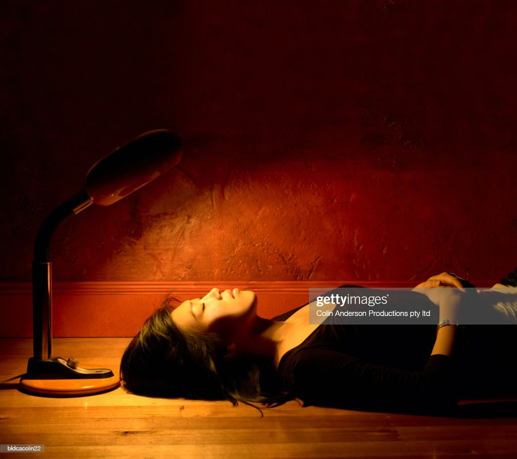 Side profile of a young woman lying on the floor : Foto de stock
