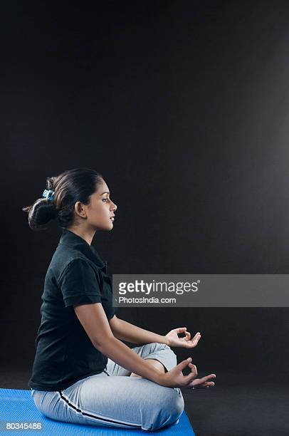 Side profile of a young woman meditating