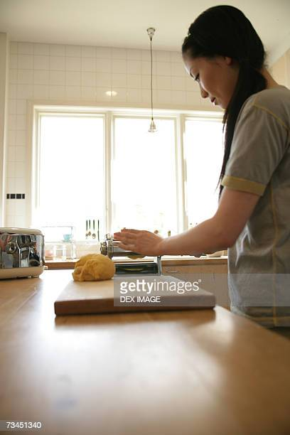 Side profile of a young woman preparing food in the kitchen