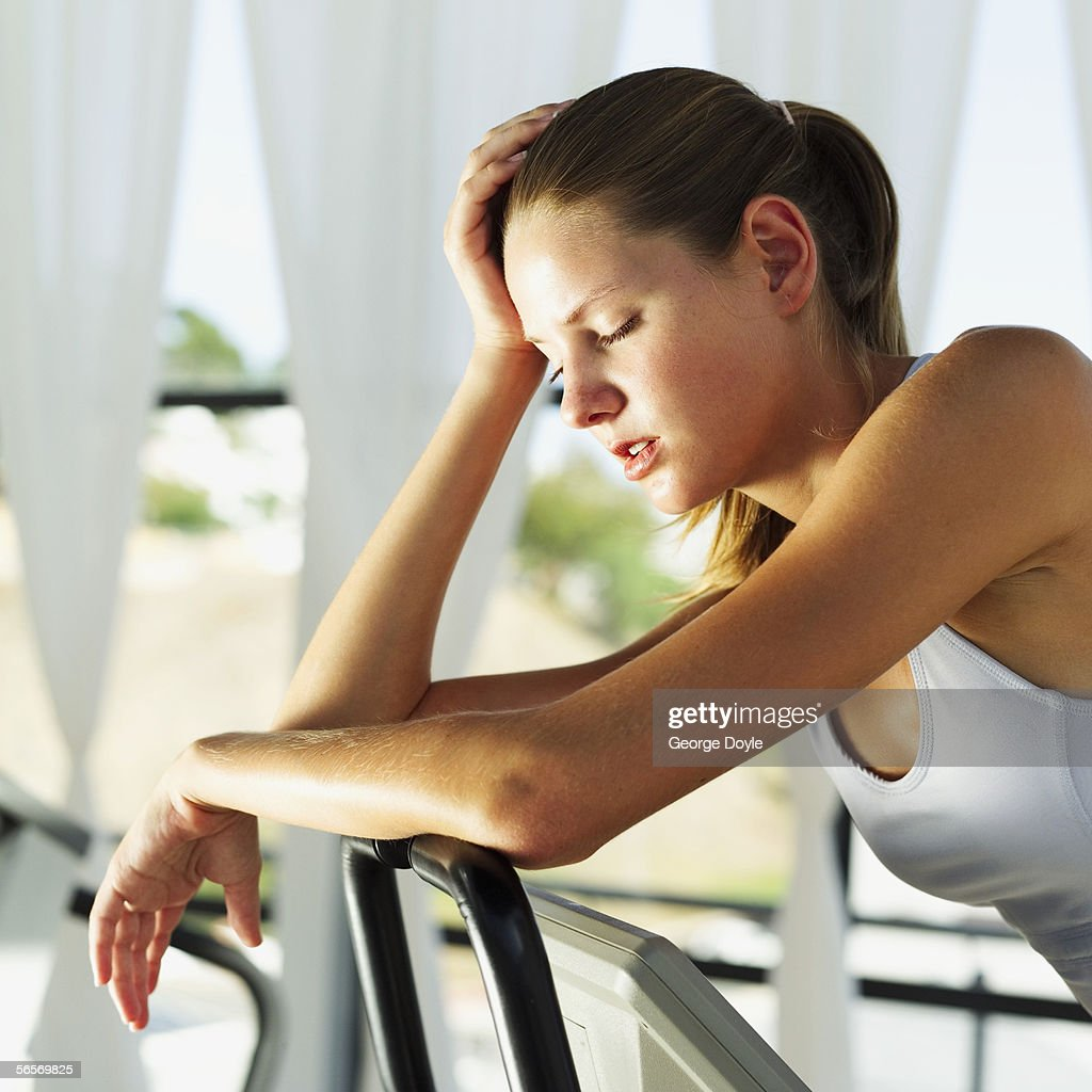 side profile of a young woman resting on the handlebars of an exercise bike : Stock Photo