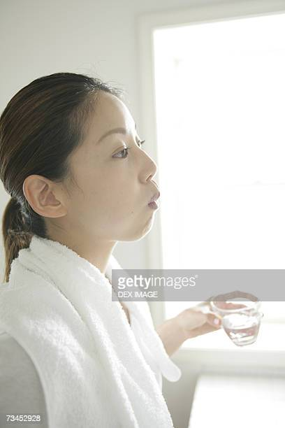 Side profile of a young woman rinsing her mouth and holding a glass of water