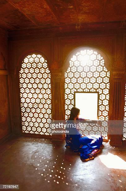 Side profile of a young woman sitting on the floor of a mausoleum, Taj Mahal, Agra, Uttar Pradesh, India