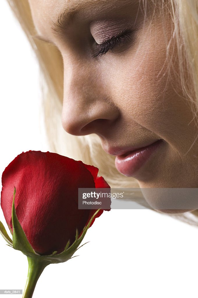 Side profile of a young woman smelling a rose : Stockfoto