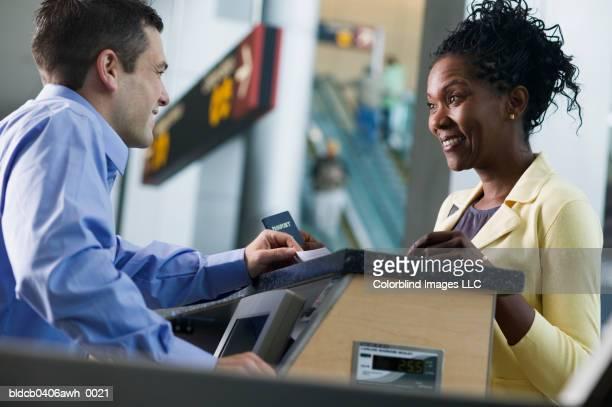 Side profile of a young woman standing across a young man at an airport counter