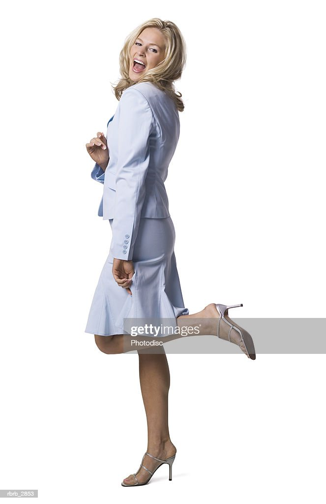 Side profile of a young woman standing with a leg raised : Foto de stock
