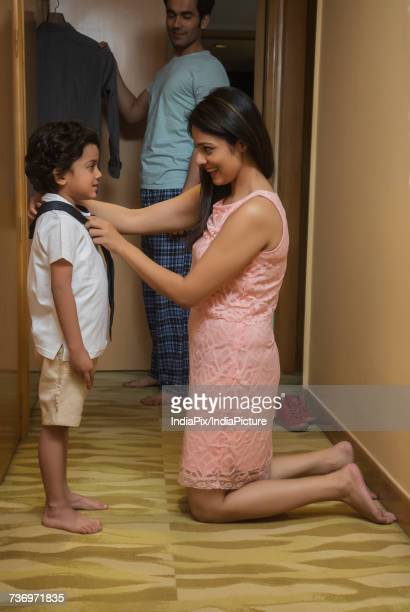 Side profile of a young woman tying her sons tie and young man looking in wardrobe