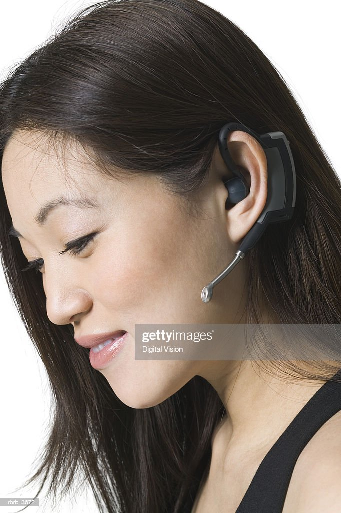 Side profile of a young woman wearing a headset : Foto de stock