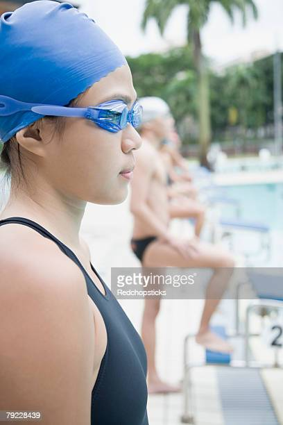 side profile of a young woman wearing swimming goggles and standing at a poolside - young men in speedos stock pictures, royalty-free photos & images
