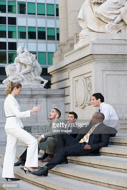 side profile of four businessmen and a businesswoman discussing on steps - human representation stock pictures, royalty-free photos & images