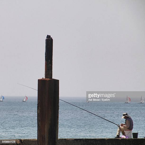side profile of man fishing at seawall - seawall stock pictures, royalty-free photos & images